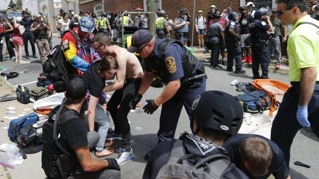 Rescue personnel help injured people after a car ran into a large group of protesters after a white nationalist rally in Charlottesville