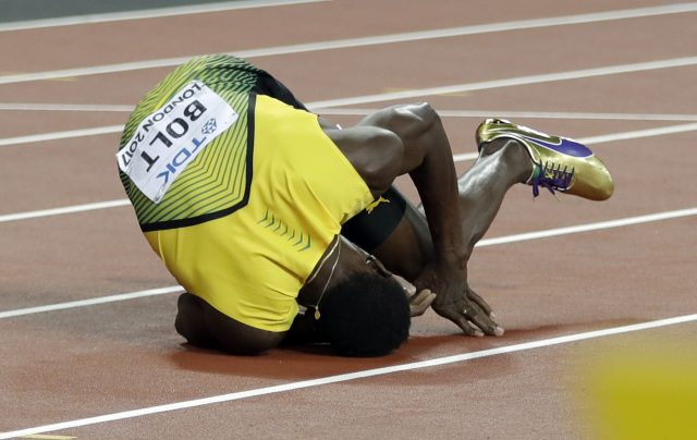Jamaica's Usain Bolt falls on the track. (Matthias Schrader/AP/PA)