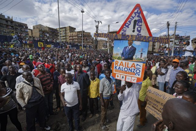 A supporter carries a placard showing Kenyan opposition leader Raila Odinga