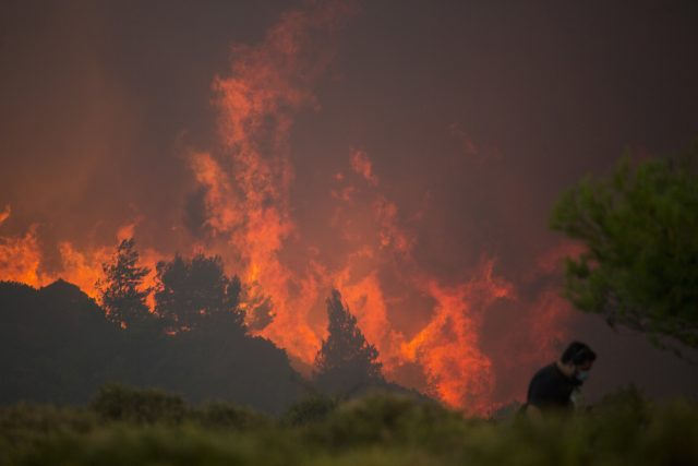 A man walks in front of huge blaze during a forest fire near the village of Varnava , north of Athens