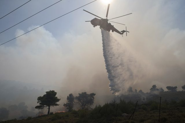 Fire burns a forest land as a helicopter drops water in the village of Varnava , north of Athens