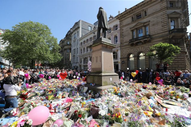 People observe a minute's silence in St Ann's Square Manchester to remember the victims of the terror attack