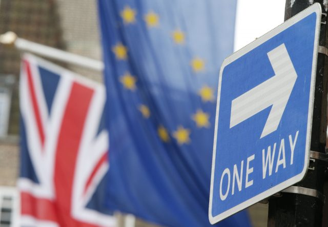 A one way sign in front of the Union and EU flags