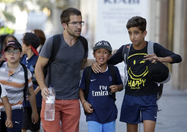 Children, some in tears, are escorted down a road in Barcelona