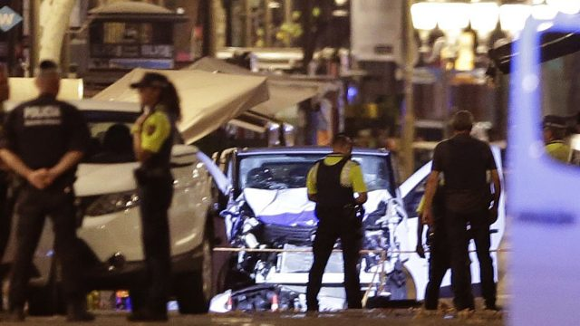 Police patrol the scene of the terrorist attack in Barcelona with the damage to the van clear to see