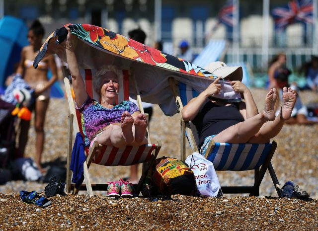 Pensioners enjoy the warm weather on the beach in Brighton, East Sussex