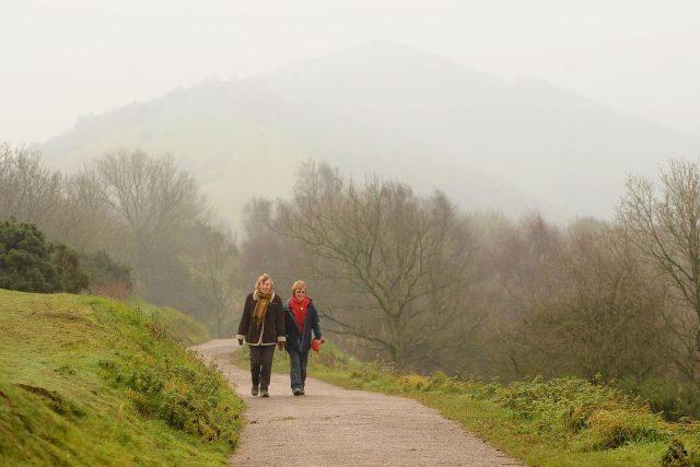 People take an early morning walk along the Malvern Hills in Worcestershire