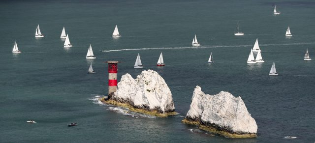 Sailing boats make their way around the Isle of Wight close to the Needles