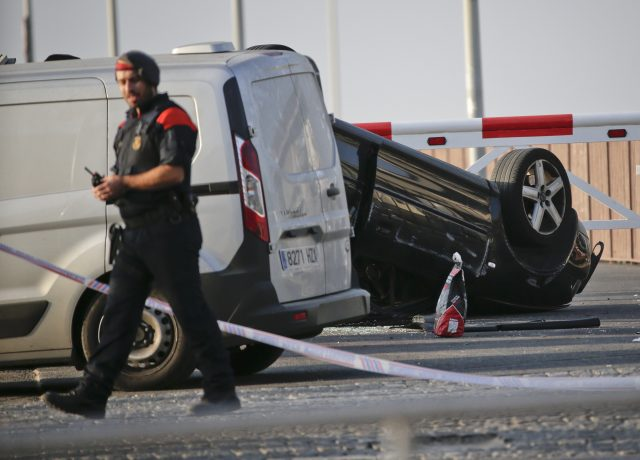 A police officer walks near an overturned car at the spot where terrorists were intercepted by police in Cambrils