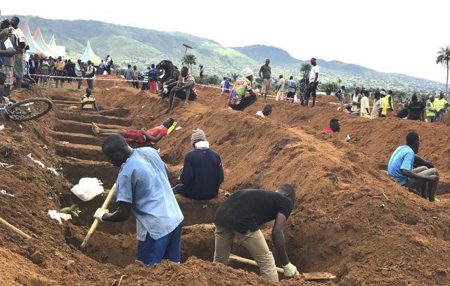 Volunteers prepare graves during a mass funeral for victims of heavy flooding and mudslides in Freetown, Sierra Leone