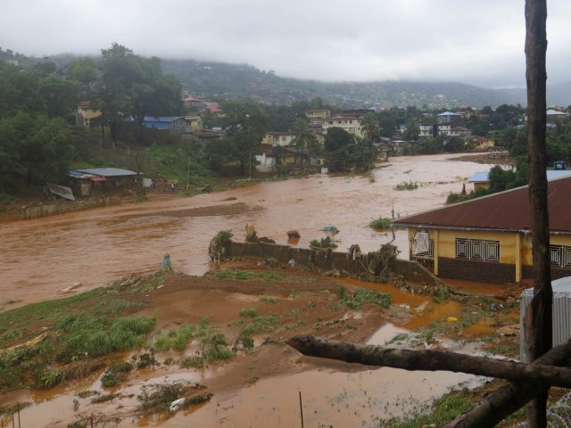 A torrent of water flows through a flooded neighbourhood in Regent, east of Freetown