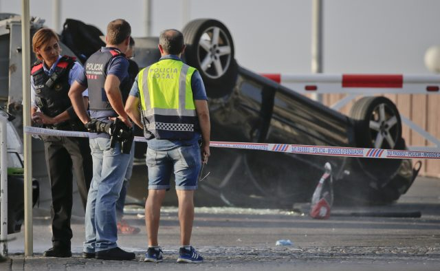 Police officers stand near an overturned car at the spot where terrorists were intercepted by police in Cambrils, Spain