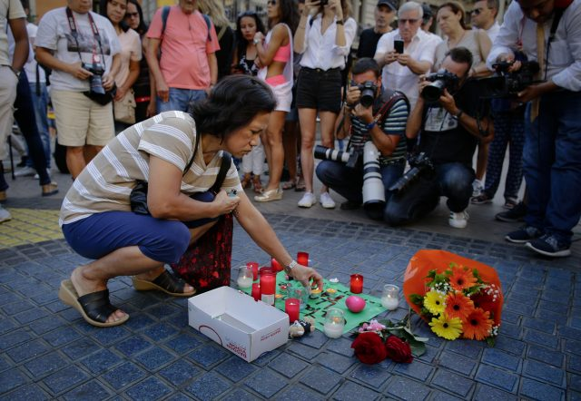 "A woman places a candle on a paper that reads ""Catalunya - place of peace"" in Las Ramblas, Barcelona"