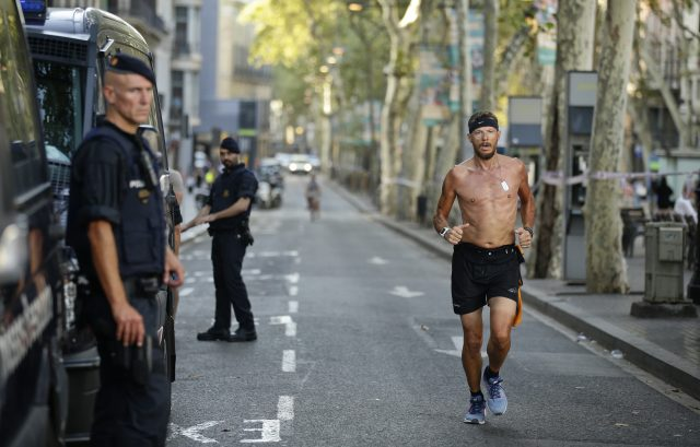 A man jogs by armed police officers standing next to their vans on a street in Las Ramblas, Barcelona
