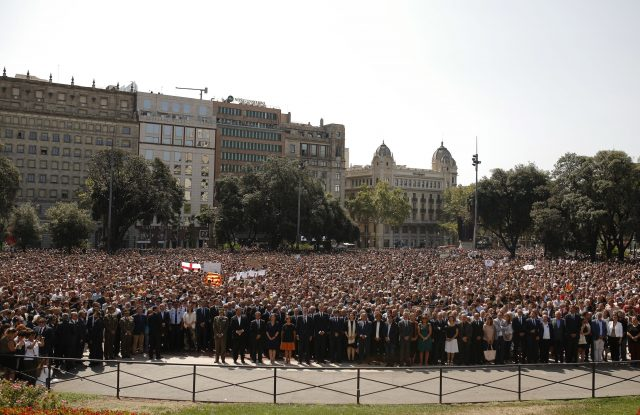 People, along with King Felipe of Spain, PM Mariano Rajoy and Catalonia regional president Carles Puigdemont observe a minute of silence in Las Ramblas