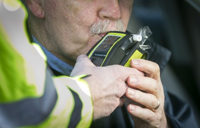 A driver blowing into a breathalyser
