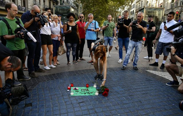 "A woman places flowers near a paper that reads ""Catalunya - place of peace"" on Las Ramblas, Barcelona"