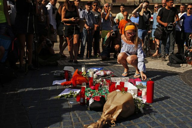 A woman places a postcard  next to bunches of flowers on Las Ramblas , Barcelona
