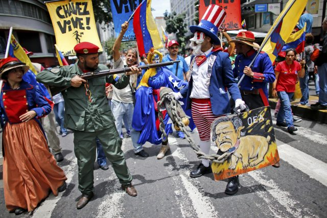 Government supporters perform a parody involving a Venezuelan militia up against Uncle Sam (Ariana Cubillos/AP)