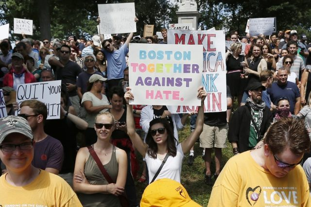 Counterprotesters hold signs at the free speech rally (Michael Dwyer/AP)