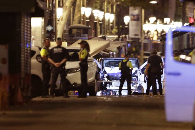 Police officers stand next to the van involved in the Barcelona attack (Manu Fernandez/AP)