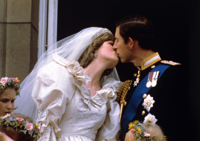 The Prince and Princess of Wales kiss on the balcony of Buckingham Palace after their wedding