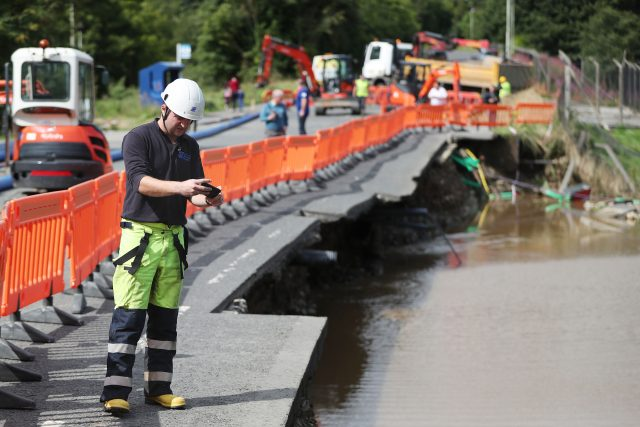 An engineer surveys damage to the road next to the river Faughan in Drumahoe, Londonderry