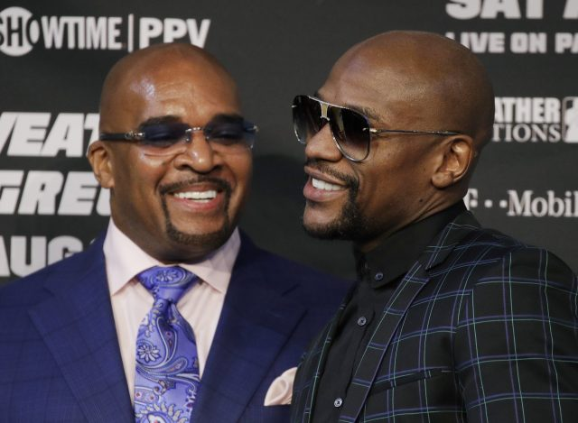 Leonard Ellerbe and Floyd Mayweather speaking at a press conference