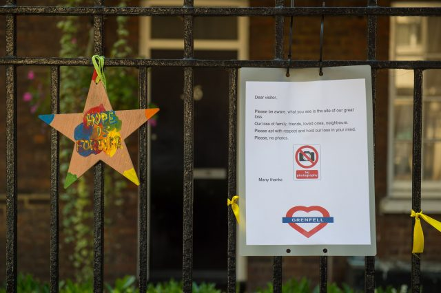 A sign asks visitors not to take photos of Grenfell Tower, in west London, with the area expecting a huge number of people during the Notting Hill Carnival