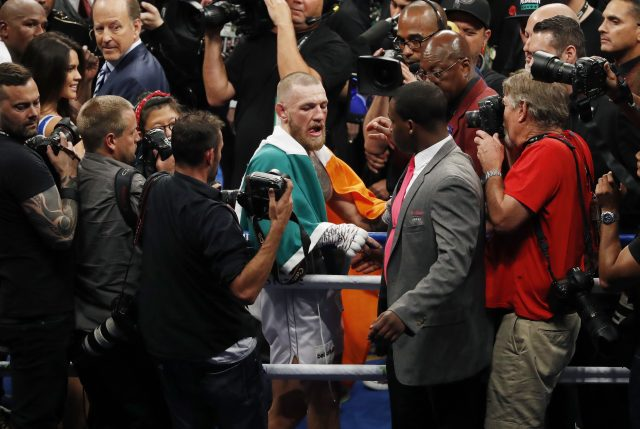 Conor McGregor, centre, reacts after losing to Floyd Mayweather Jr