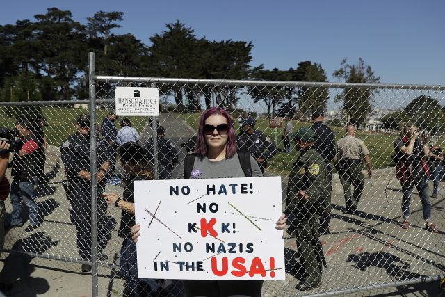 Andrea Smith holds up a sign in front of a fence blocking an entrance to Alamo Square Park in San Francisco