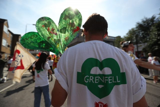 People wearing T-shirts and holding flags honouring the memory of the victims of the Grenfell Tower fire during the final day of the Notting Hill Carnival