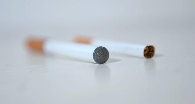 An e-cigarette next to a normal cigarette