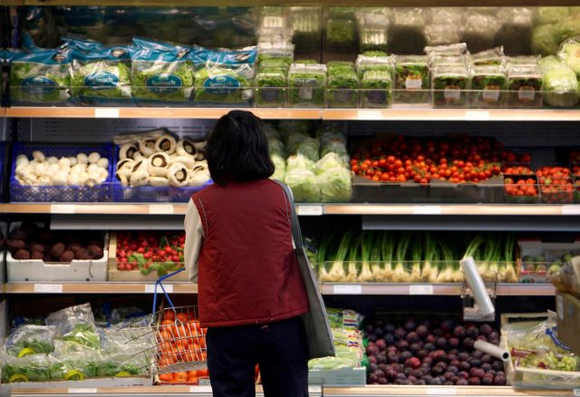 A shopper selects vegetables in a supermarket