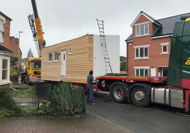 A micro-home is lifted off the back of a lorry