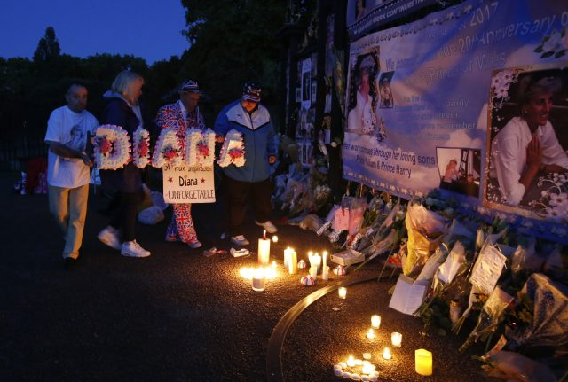 Tributes, candles and flowers are laid by royal fans outside Kensington Palace (Alastair Grant/AP)