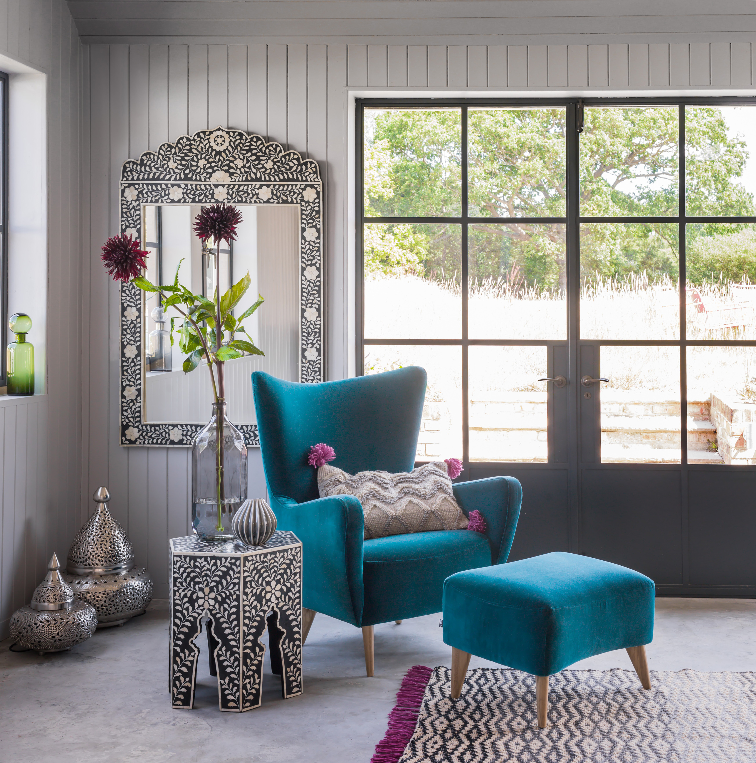 Elsa Chair In Luxe Turquoise Velvet, £1,095; Footstool, £398; Adriana Mirror, Grey, £495; Zagora Table, £279, Graham & Green (Graham & Green/PA)
