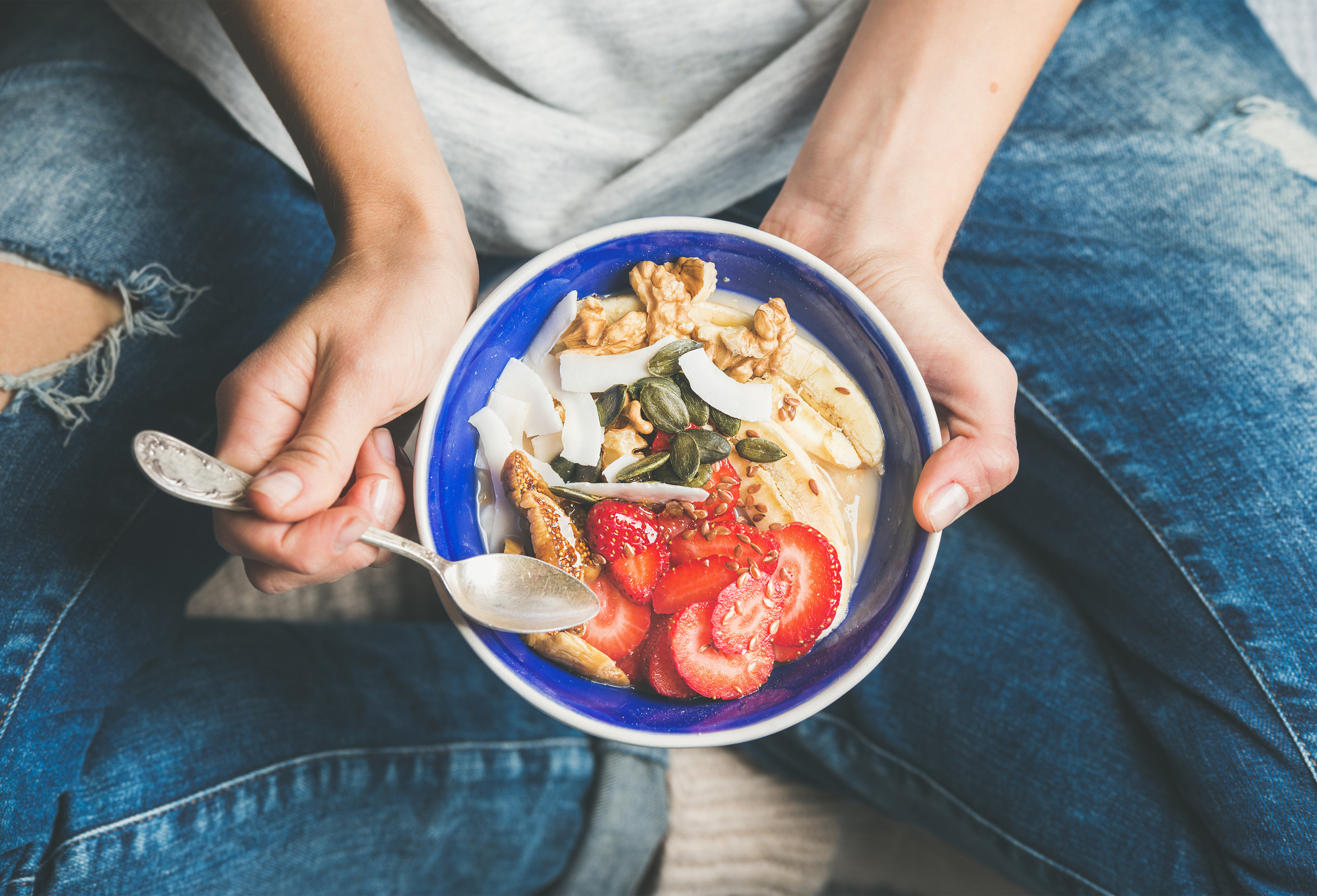 Generic photo of woman sat on the floor eating bowl of healthy food (Thinkstock/PA)