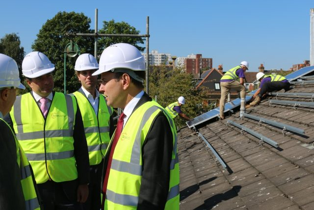 International Trade Minister Greg Hands visiting a social housing development in Ealing. (PA)