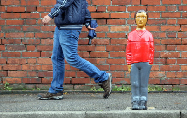 A man walks past a life-sized child shaped bollard