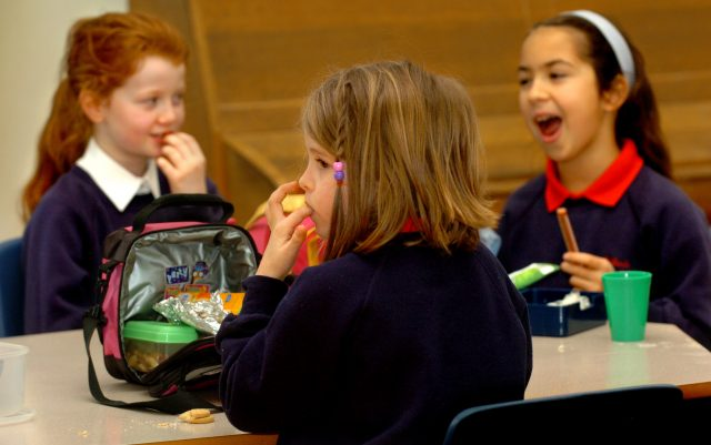 Pupils eating their packed lunches at school