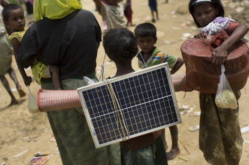 A Rohingya Muslim child carries a solar panel as she crosses over the border (Bernat Armangue/AP)