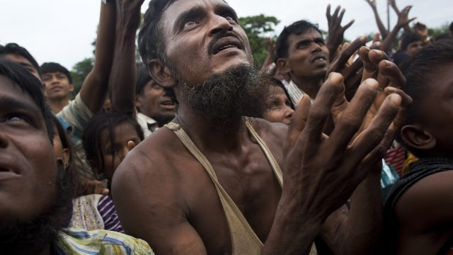 A Rohingya man stretches his arms out for food distributed by local volunteers at Kutupalong