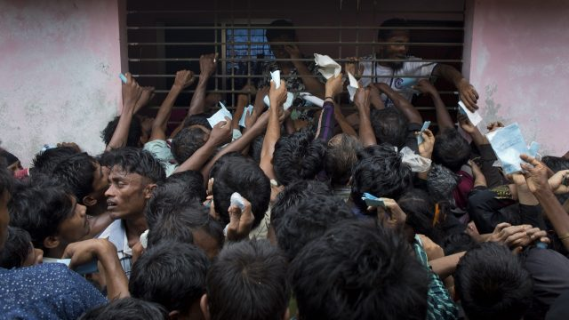 Newly arrived Rohingya try to get their tokens validated in order to collect a bag of rice