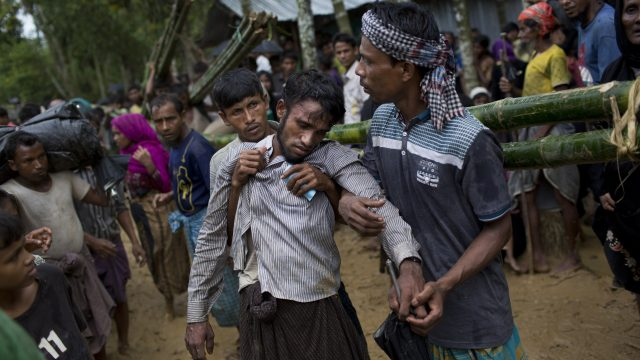 Kifawet Ullah is helped by other newly arrived Rohingya after he collapsed while waiting to have his token validated in order to collect a bag of rice