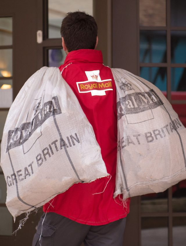 A postman carrying bags of mail