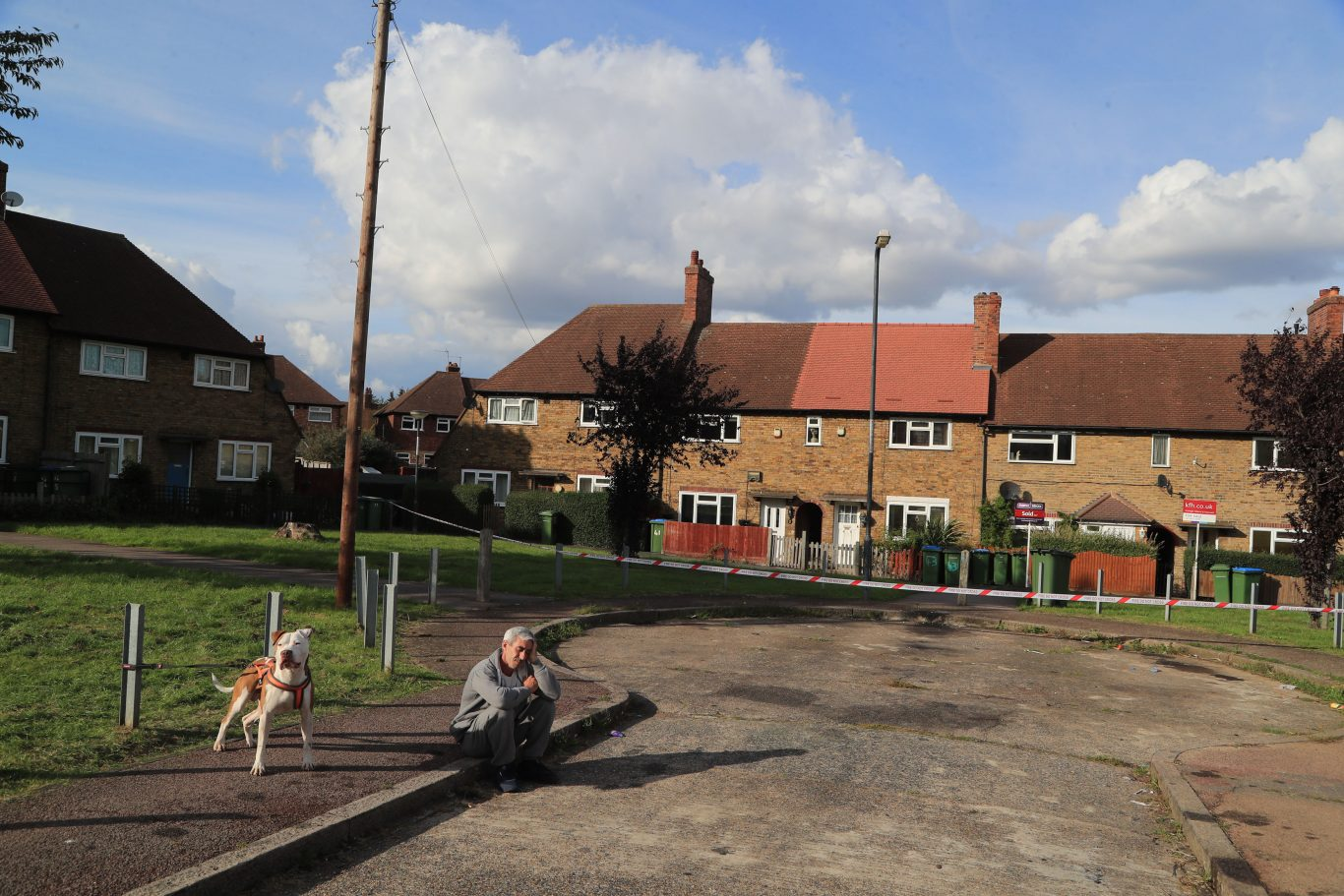 A man and his dog next to a cordon put in place by fire crews at Alwold Crescent in Lee, south London (Gareth Fuller/PA)