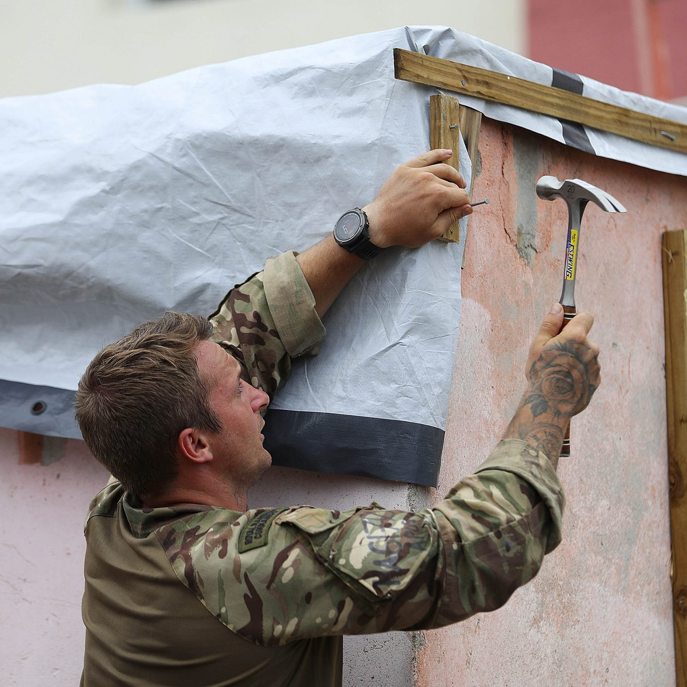 Marine Jordan Harding of 40 Commando Royal Marines helping to fix up Alvin and Dorothy Nibbs' house in Road Town, Tortola (Ministry of Defence/PA)