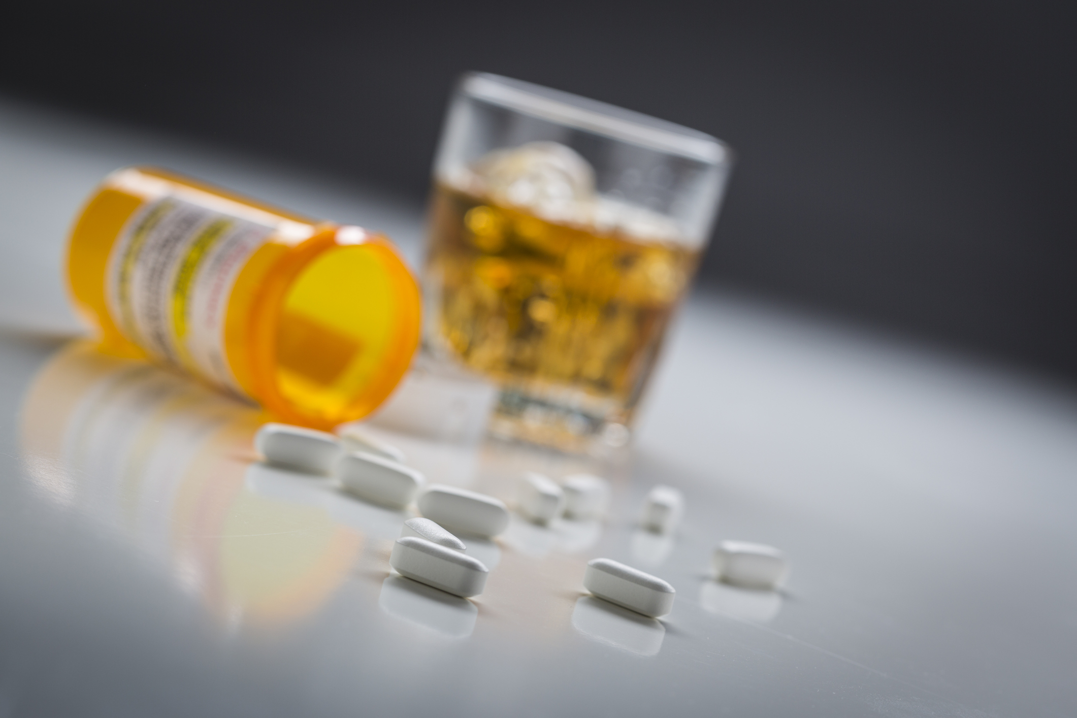 Prescription drugs spilled from fallen bottle near glass of alcohol (Thinkstock/PA)