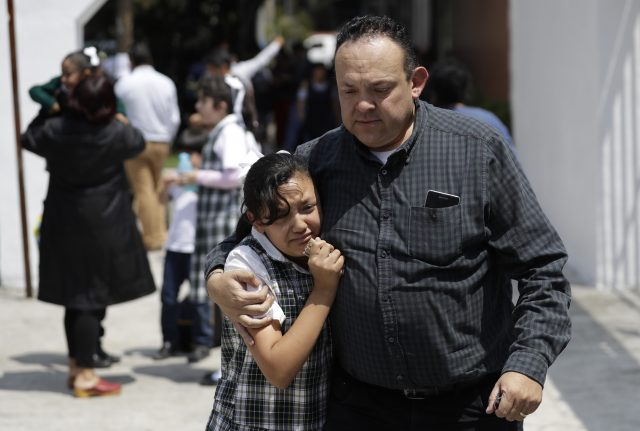 A man comforts a frightened student as he collects her from her school in the Roma neighborhood of Mexico City (Rebecca Blackwell/AP)